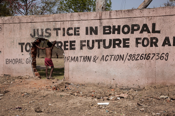 A boy stands by a hole in her wall surrounding the derelict Union Carbide factory in Bhopal. Photo by David Graham